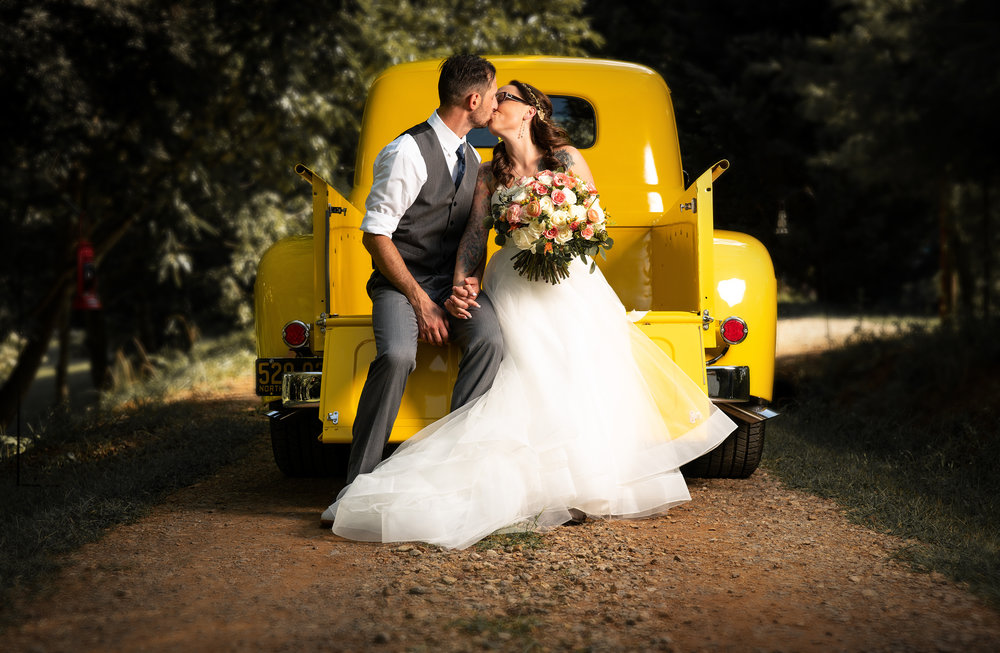 Asheville wedding couple kissing on a yellow car.