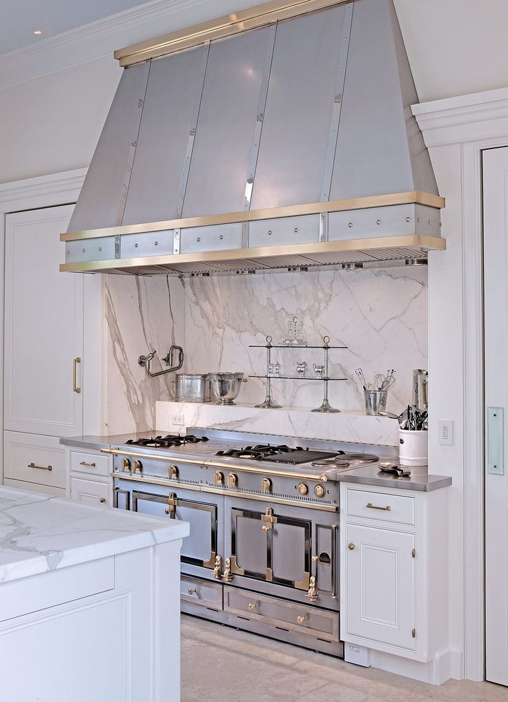 This range and hood combination by St. Charles New York acts more as an art piece in this kitchen.  The stainless and polished nickel metal finish combo adds just enough of the unexpected in this timeless space. Image Via St. Charles New York.