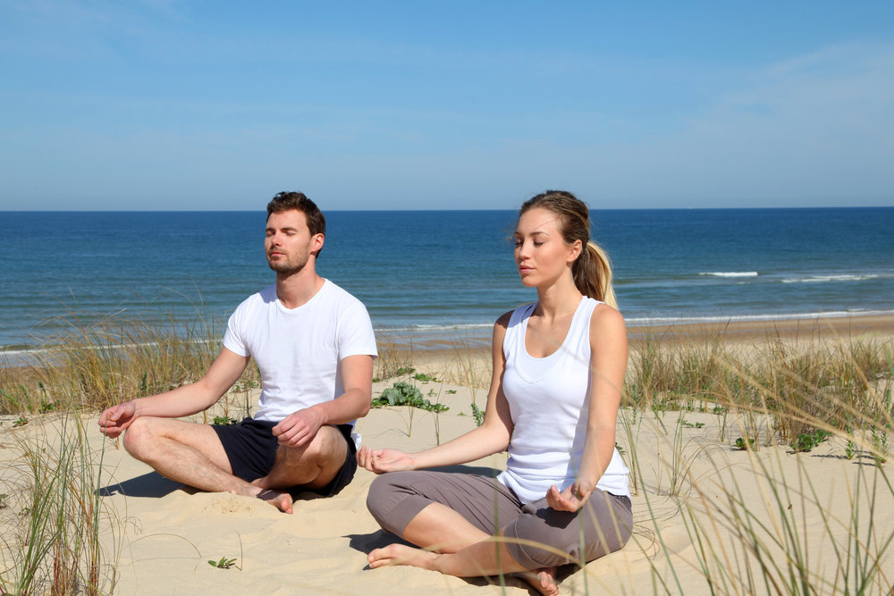 YOUNG COUPLE MEDITATING ON BEACH.jpeg