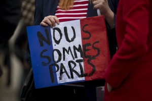 "A woman holds a French flag colored placard with French translating as ""we are Paris"" whilst attending a vigil for victims of the deadly Paris attacks, in Trafalgar Square, London, Saturday, Nov. 14, 2015. French President Francois Hollande said more than 120 people died Friday night in shootings at Paris cafes, suicide bombings near France's national stadium and a hostage-taking slaughter inside a concert hall. (AP Photo/Matt Dunham)/LMD124/263092334897/1511141544"