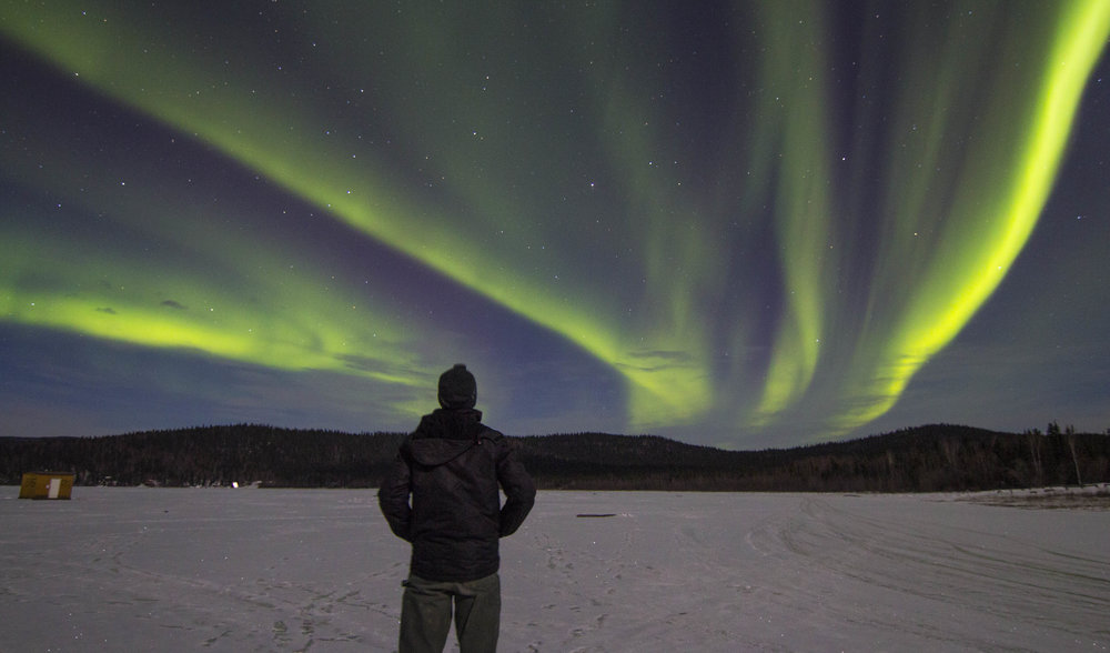 Overlooking a northern lights show on a frozen lake in interior Alaska