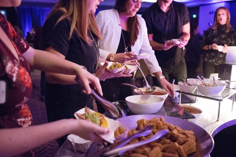 Attendees grab food from the taco bar and churro station before the start of the show.