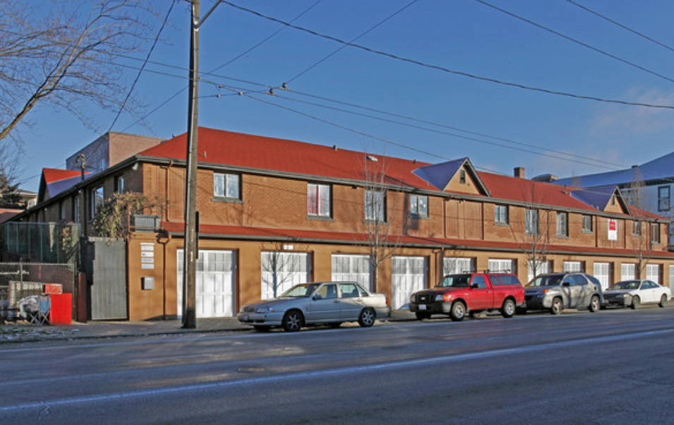 Side view with garages (now used for micro-businesses) and entry to basement makerspace.