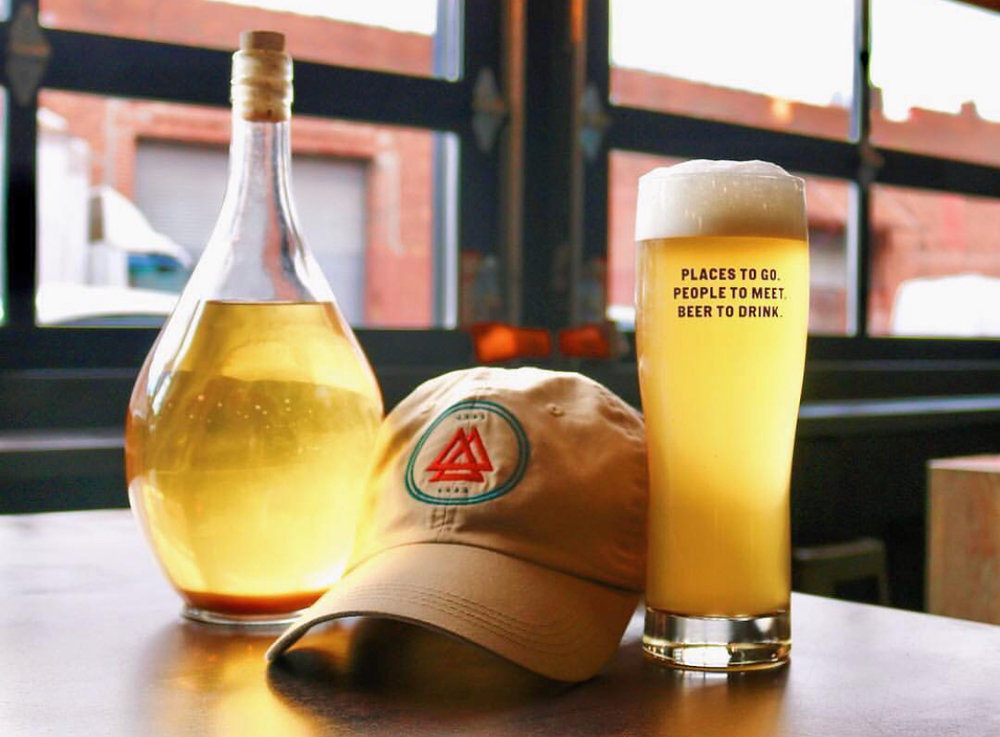Bottled of Honey Lager next to an All-Wise cap and a cup of honey lager
