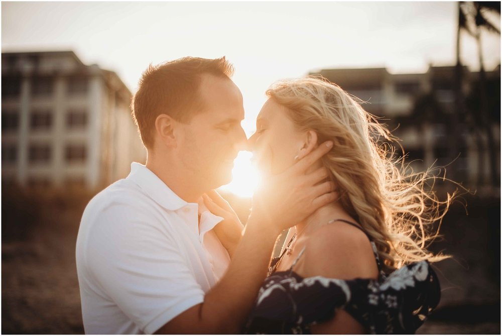 couple kissing sunlight peeking through