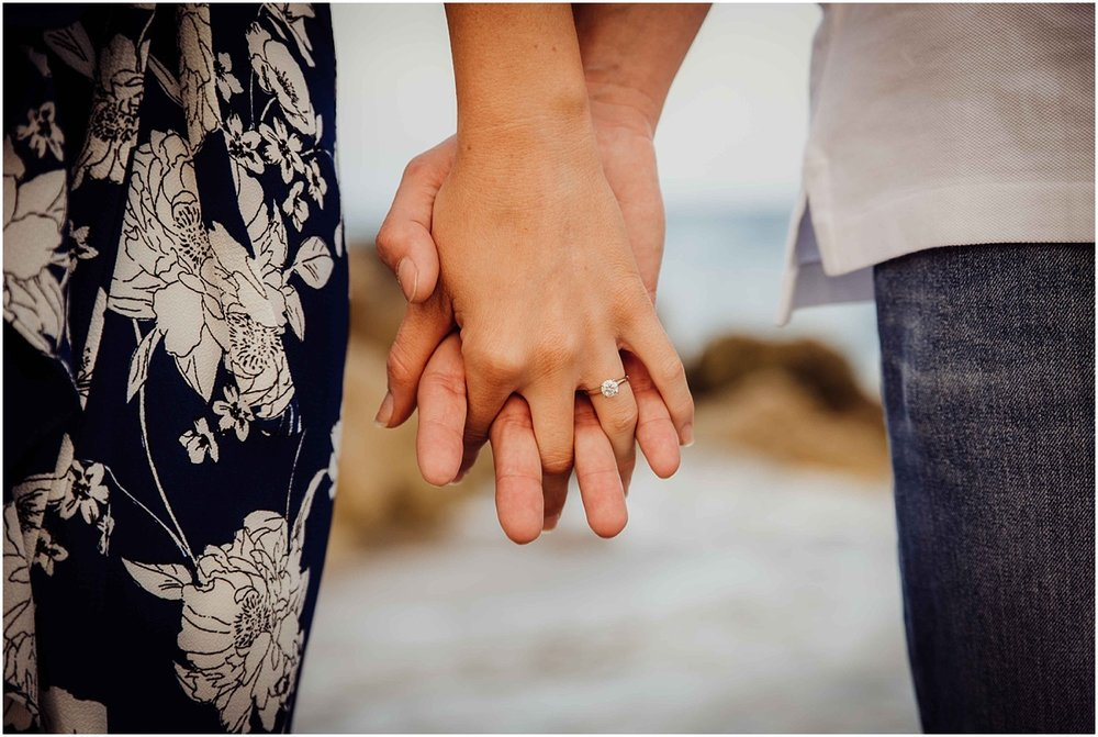 holding hands on beach engagement ring