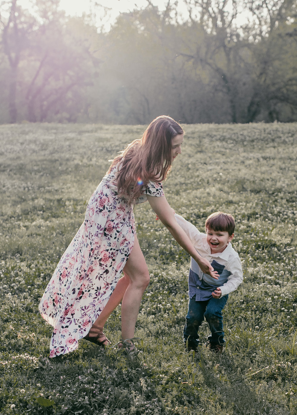 mom and son dancing in field