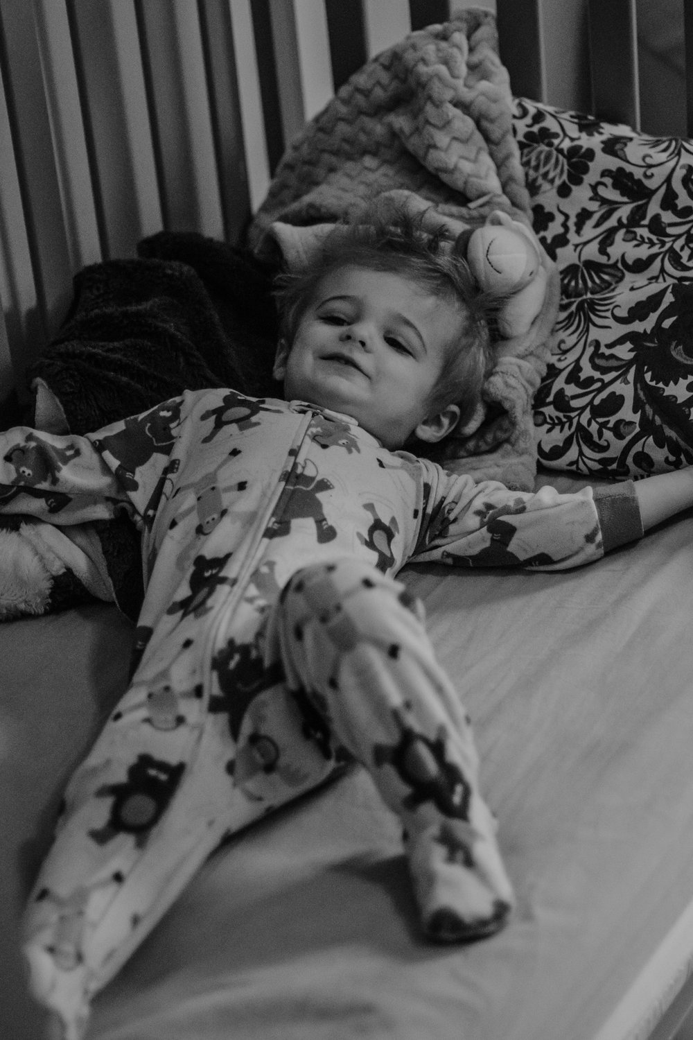toddler laying in bed