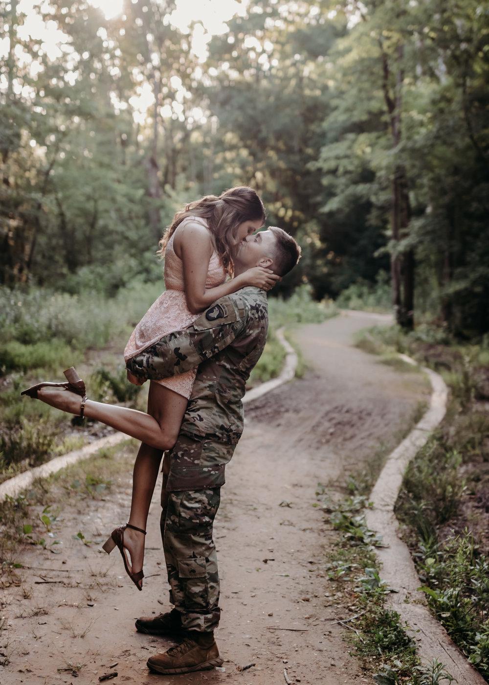 man in uniform raising girl up kissing