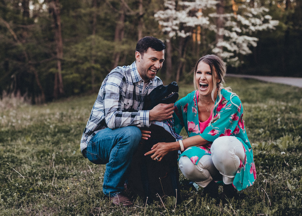 couple with dog in love laughing