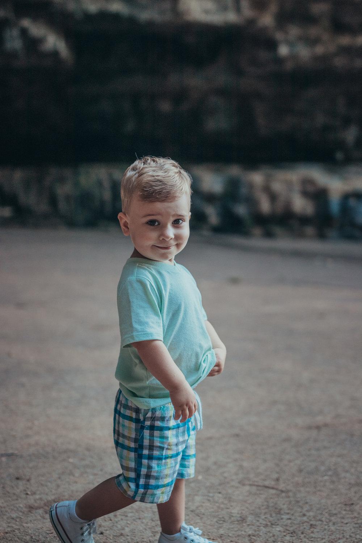 toddler boy walking and smiling