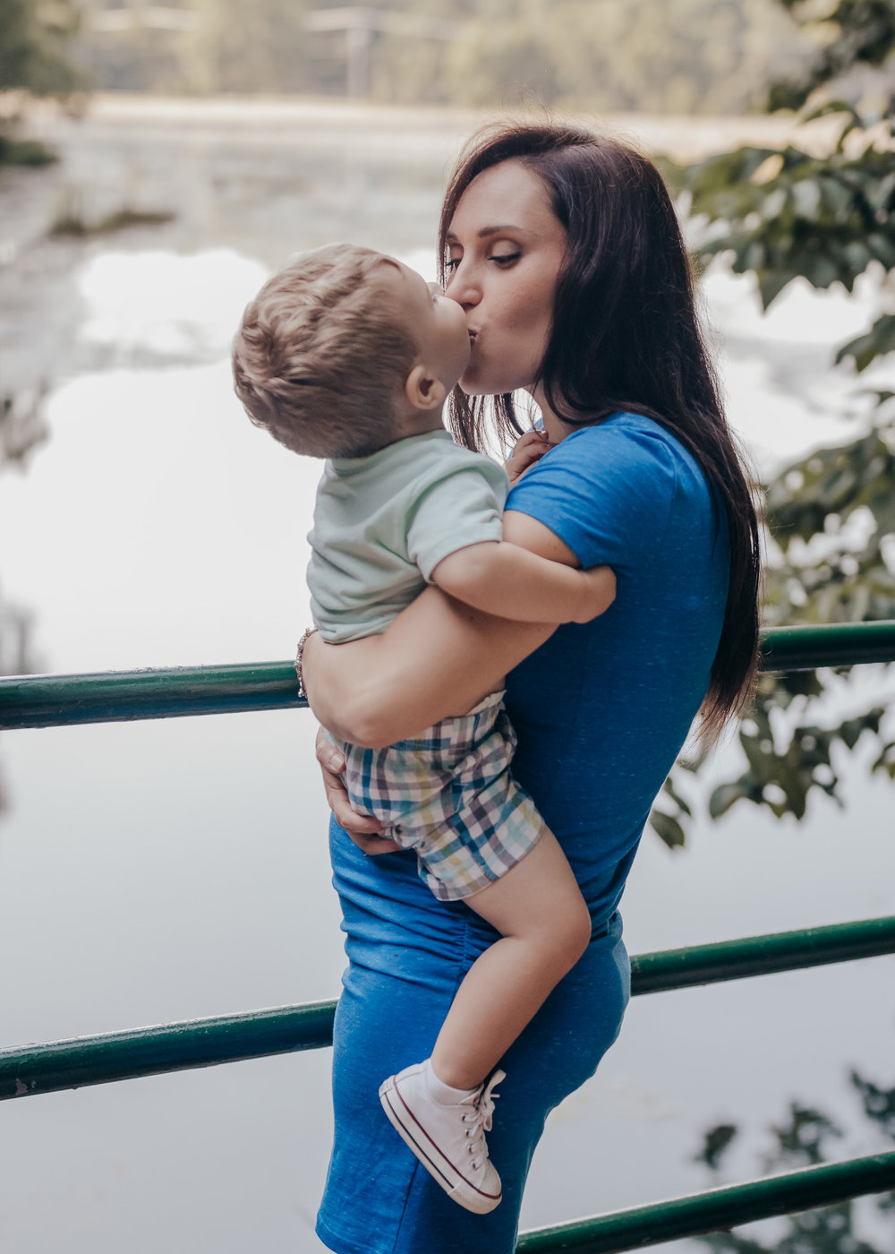 mom and son kissing by water