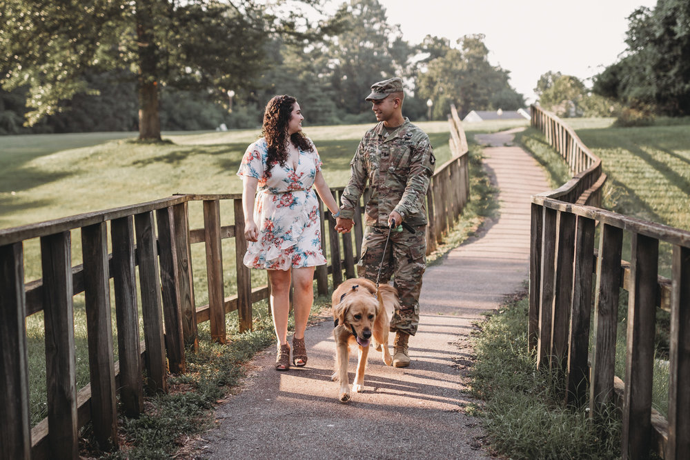 army man in uniform walking with wife and dog