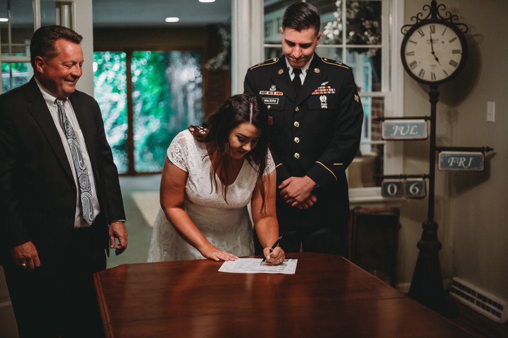 bride signing wedding paperwork