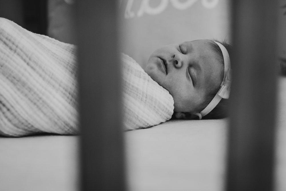 black and white newborn baby in crib