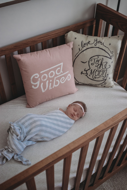 newborn baby girl in crib sleeping