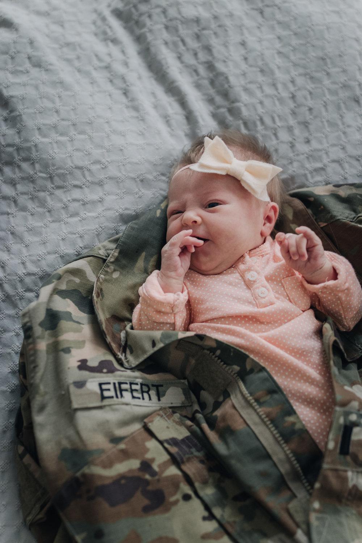newborn with military uniform around her