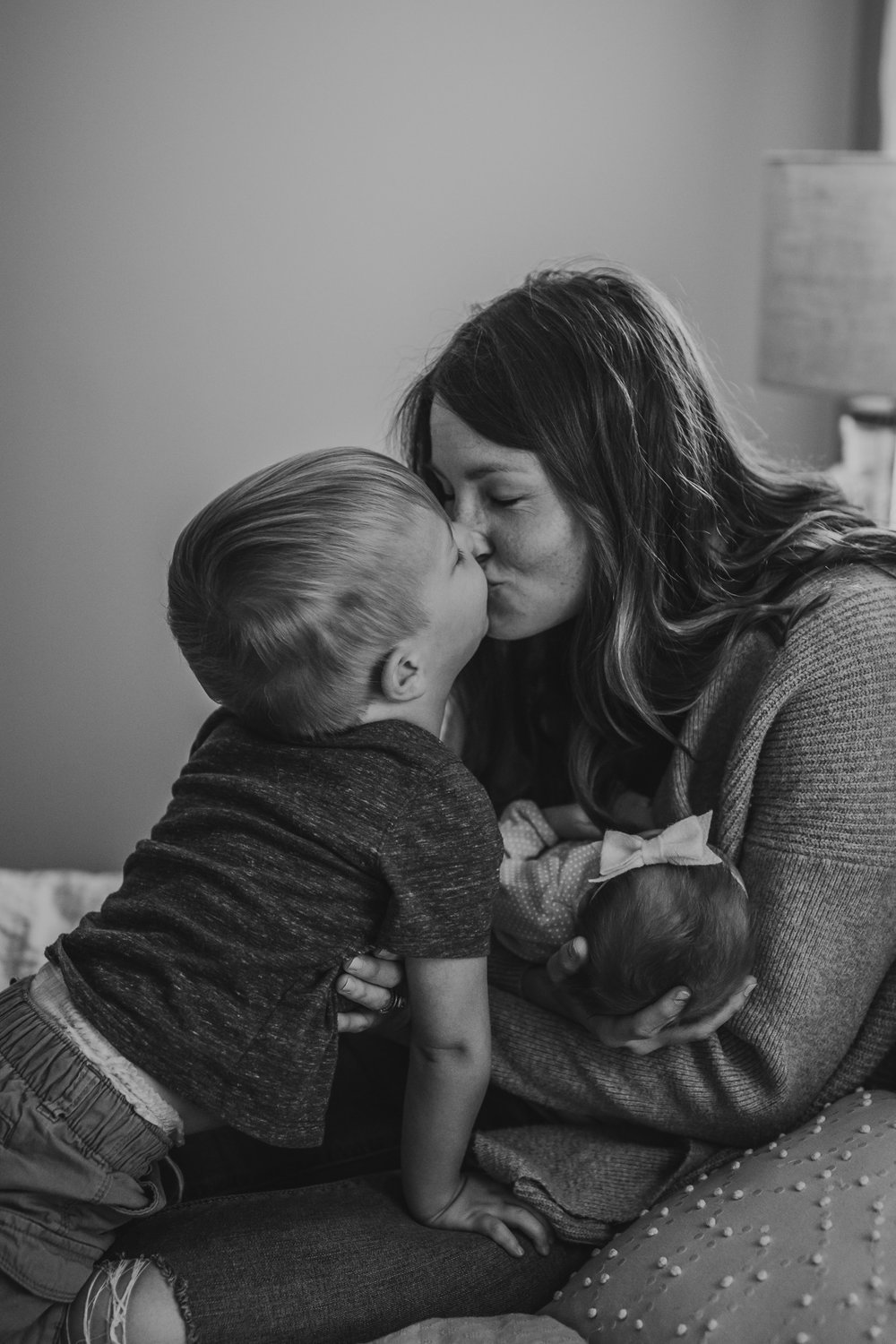 mom kissing toddler while holding newborn