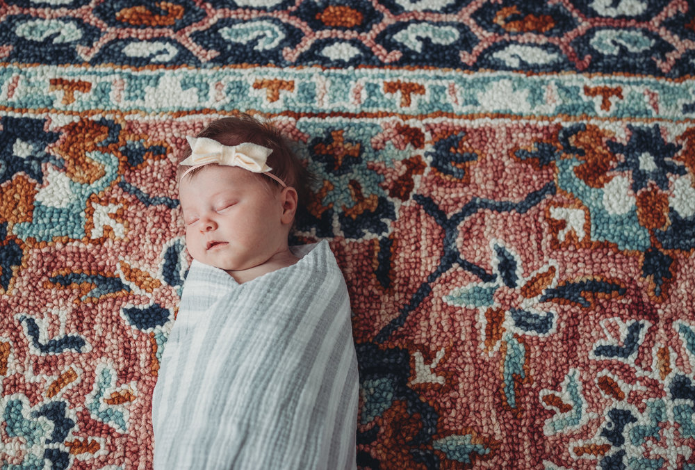 swaddled newborn baby on colorful rug