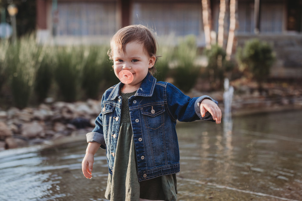 child in water with pacifier