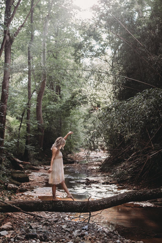 girl walking on log over creek outdoor boudoir
