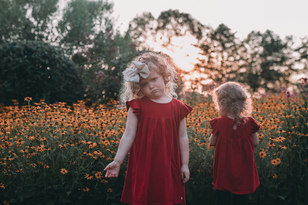 little girls in flowers at sunset