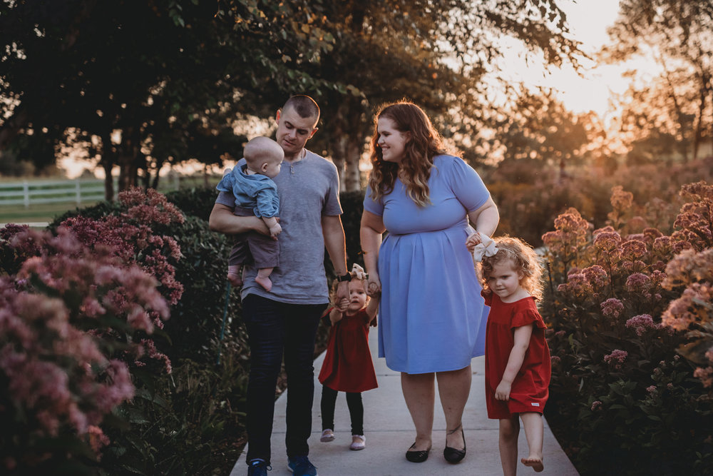 family walking in sunset around flowers