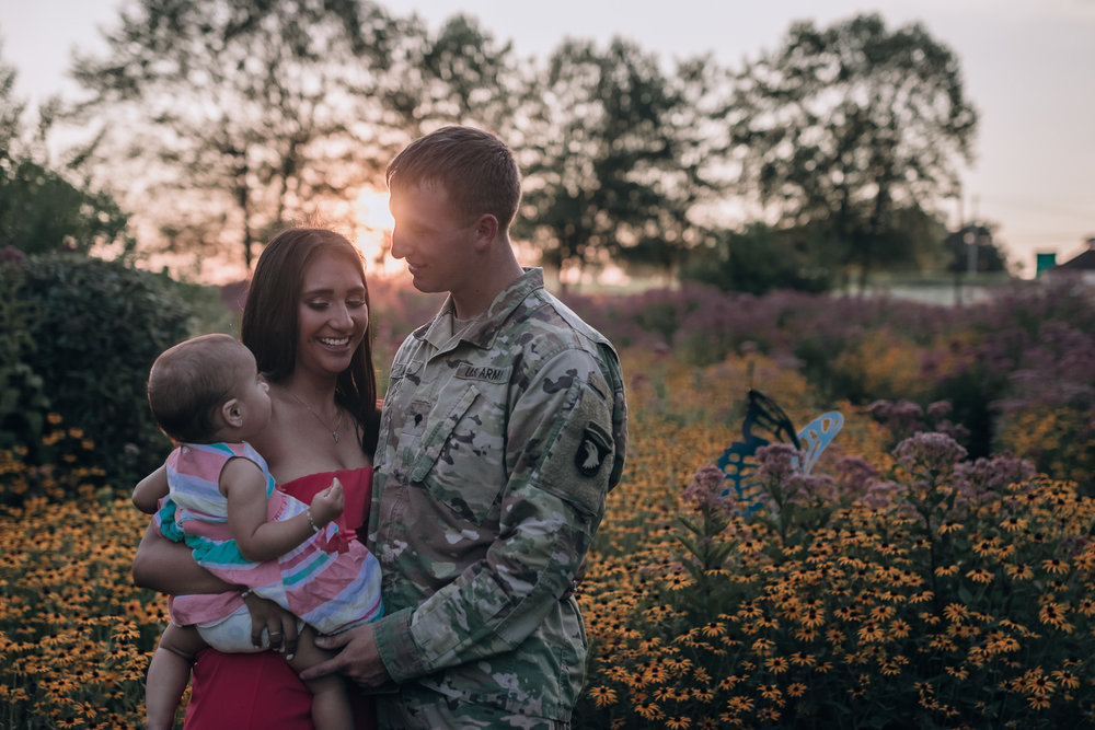 mom and dad with baby in sunset