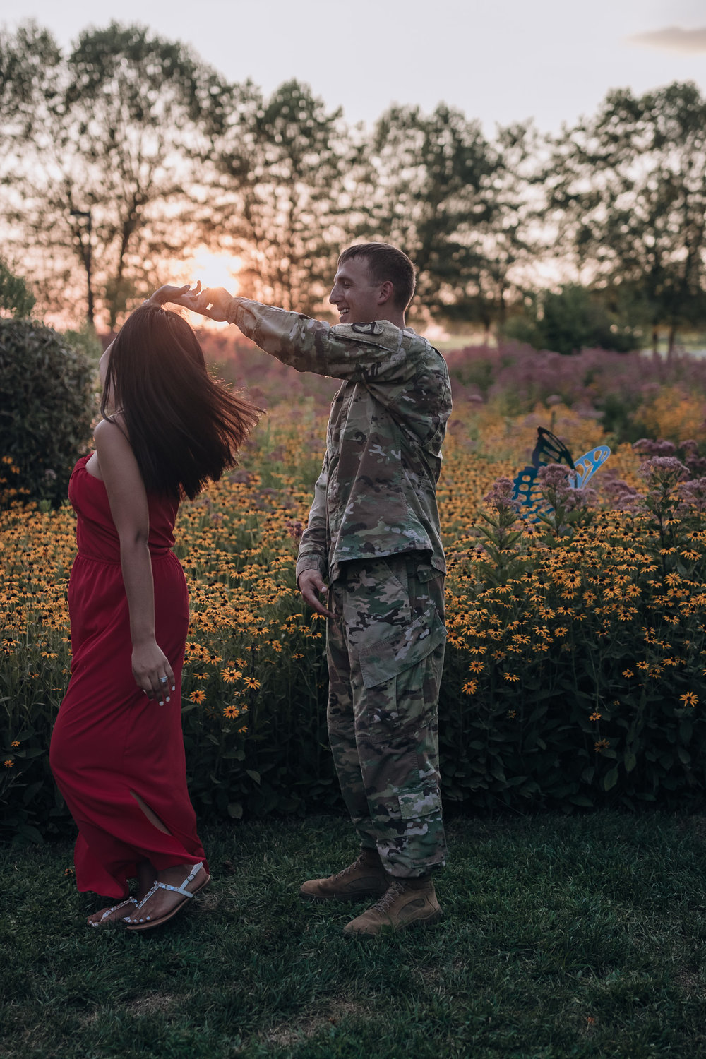 couple dancing in flower fields at sunset