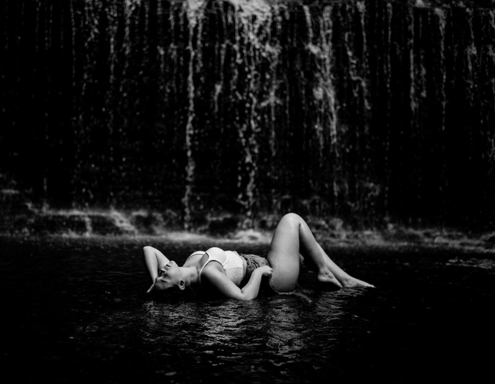 black and white photo of girl laying in water in front of waterfall