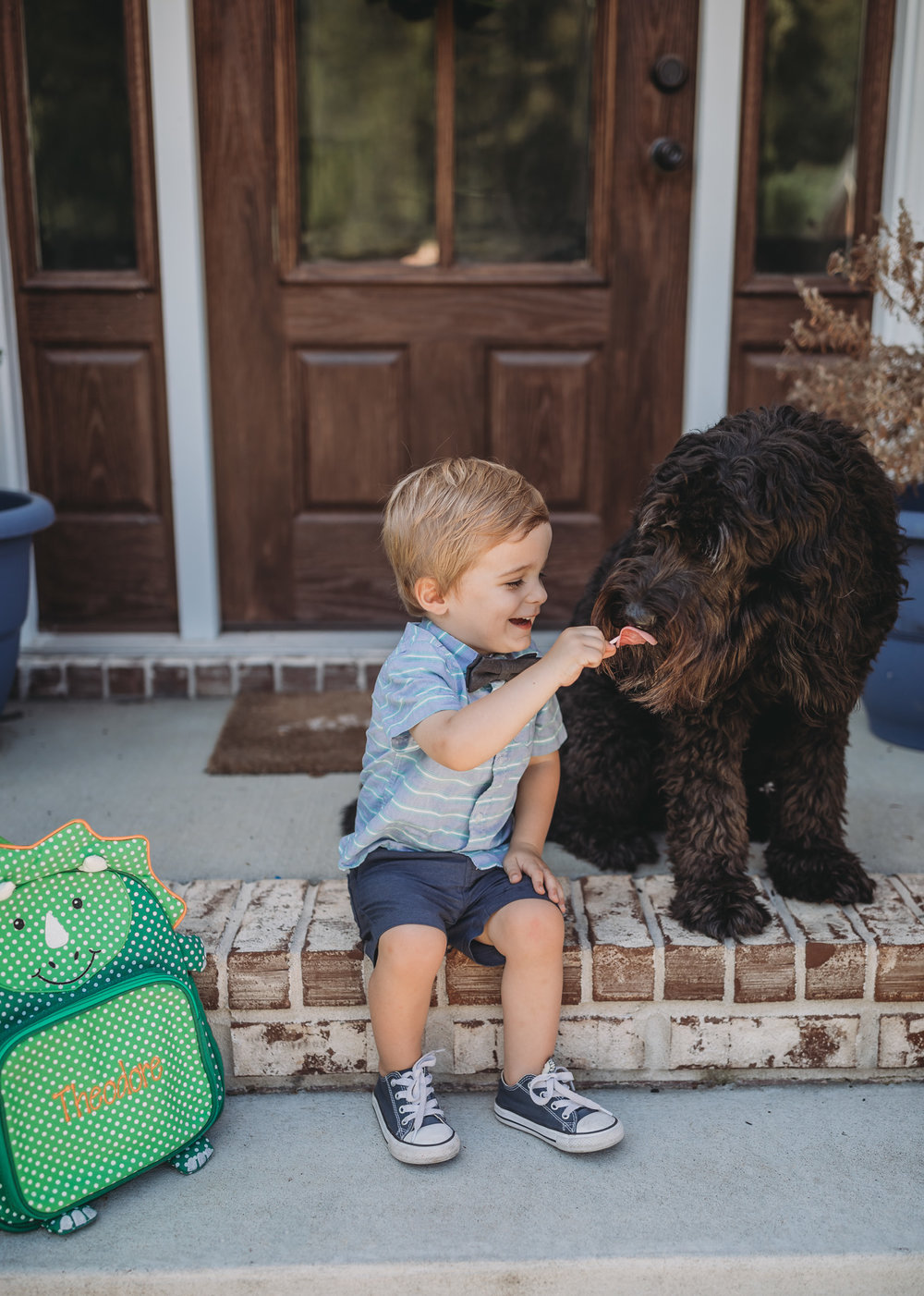 toddler sharing treat with dog