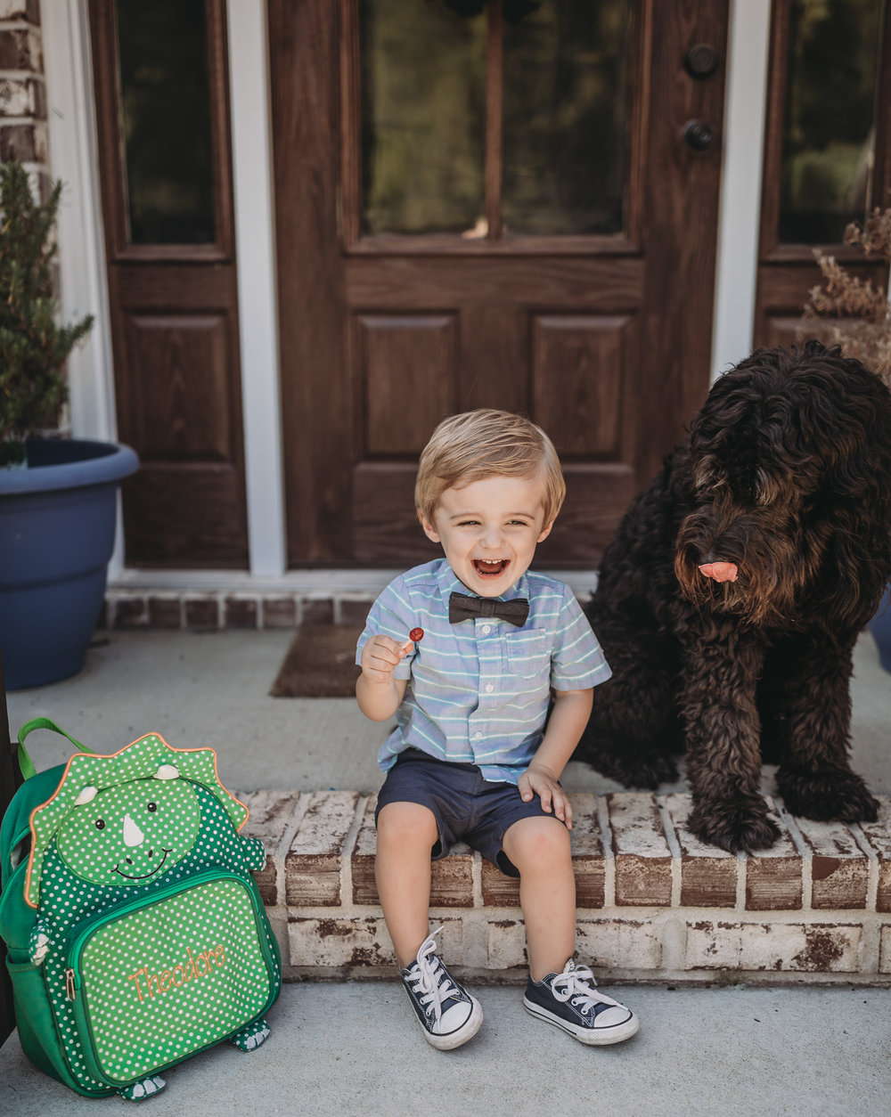 child with black goldendoodle