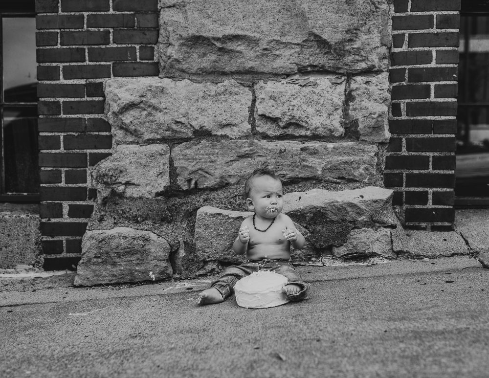 black and white photo of baby with cake