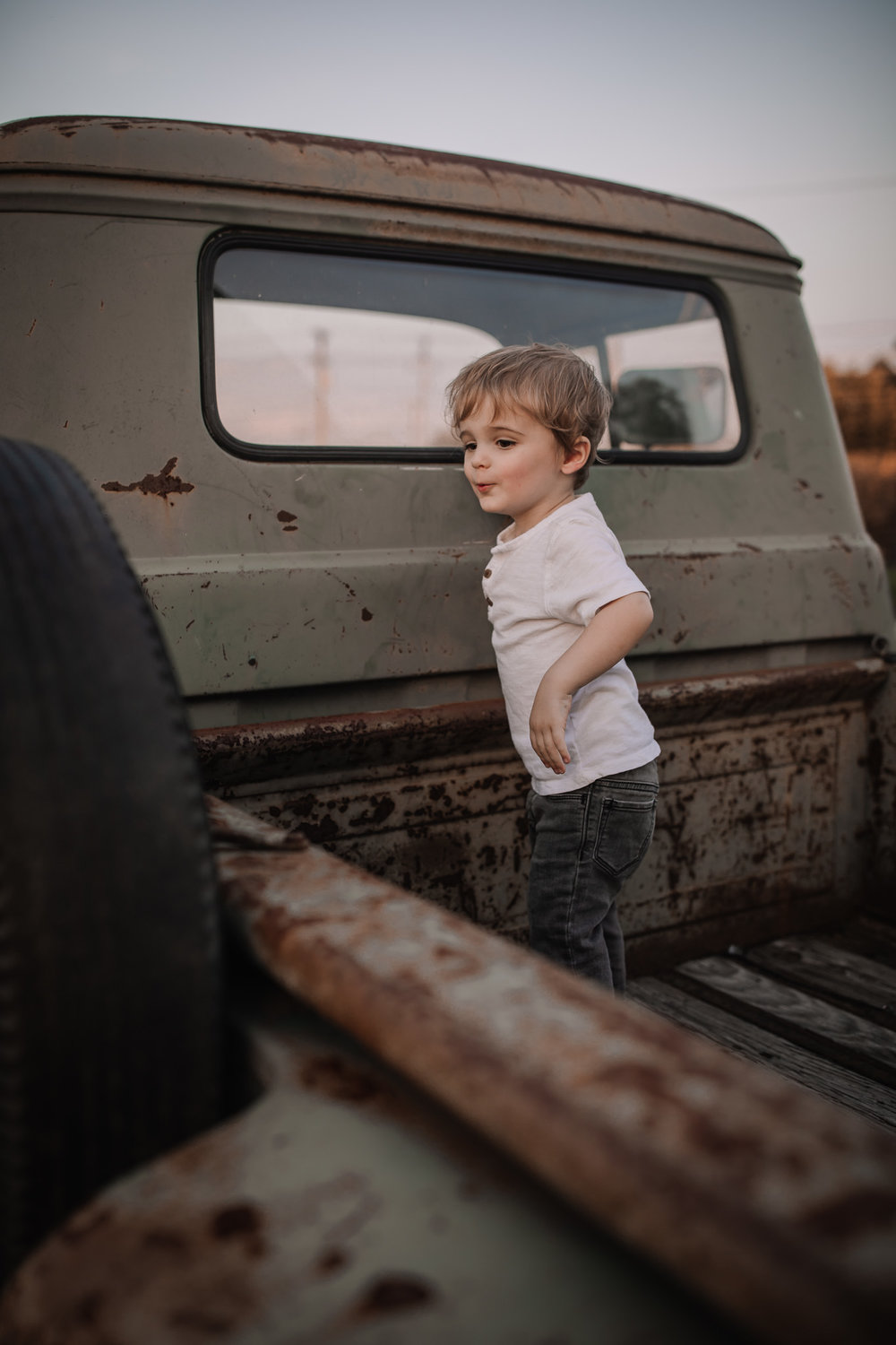 toddler standing in vintage truck