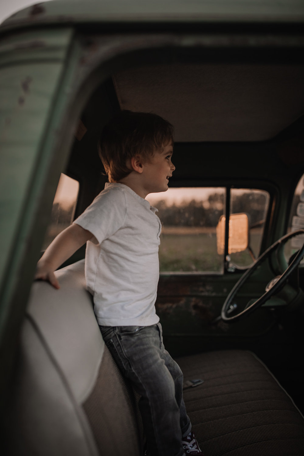toddler boy standing in vintage truck