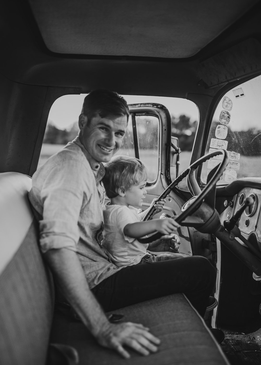 father and son black and white photo in vintage truck