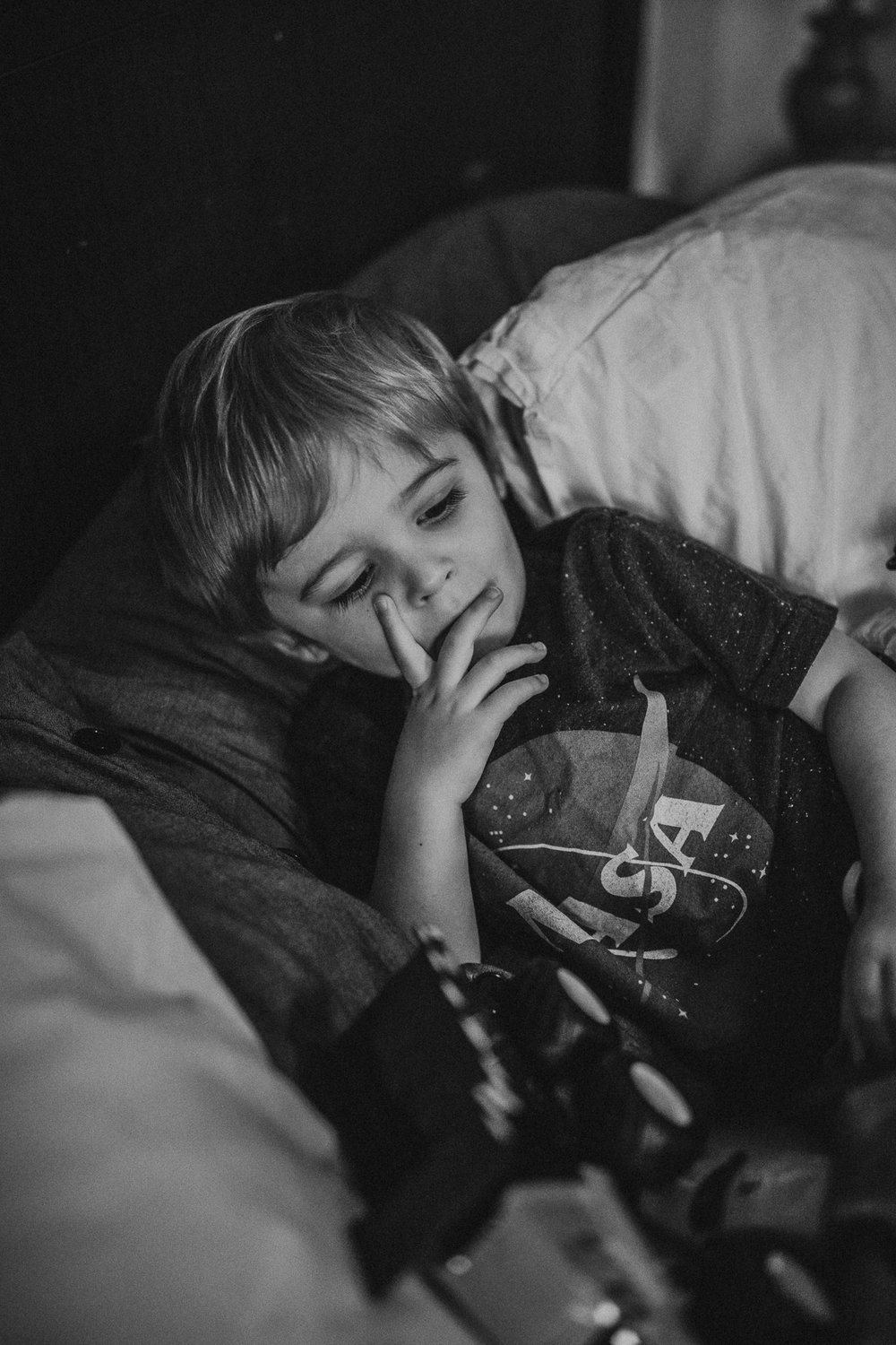 black and white of little boy in bed