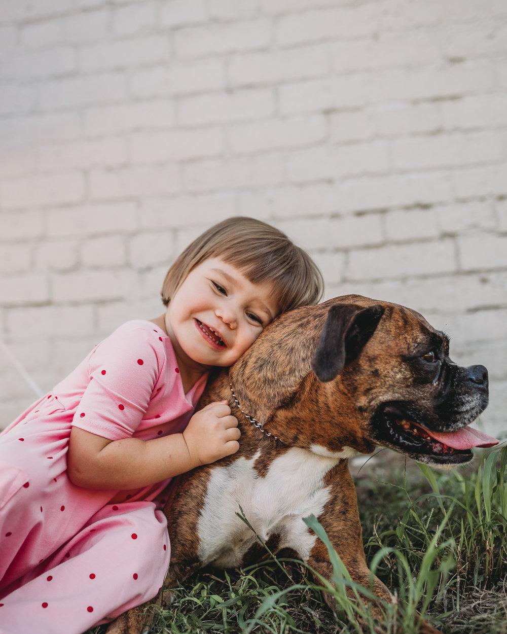 little girl hugging boxer dog