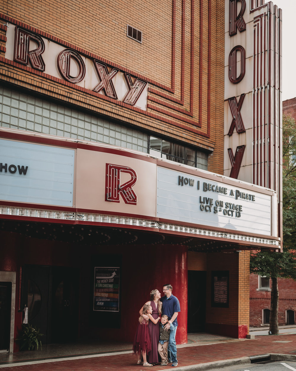 family in front of Roxy theater