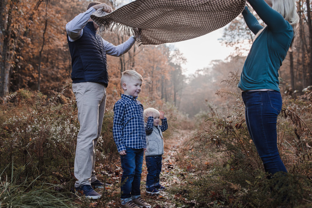 toddler boys playing parachute with blanket