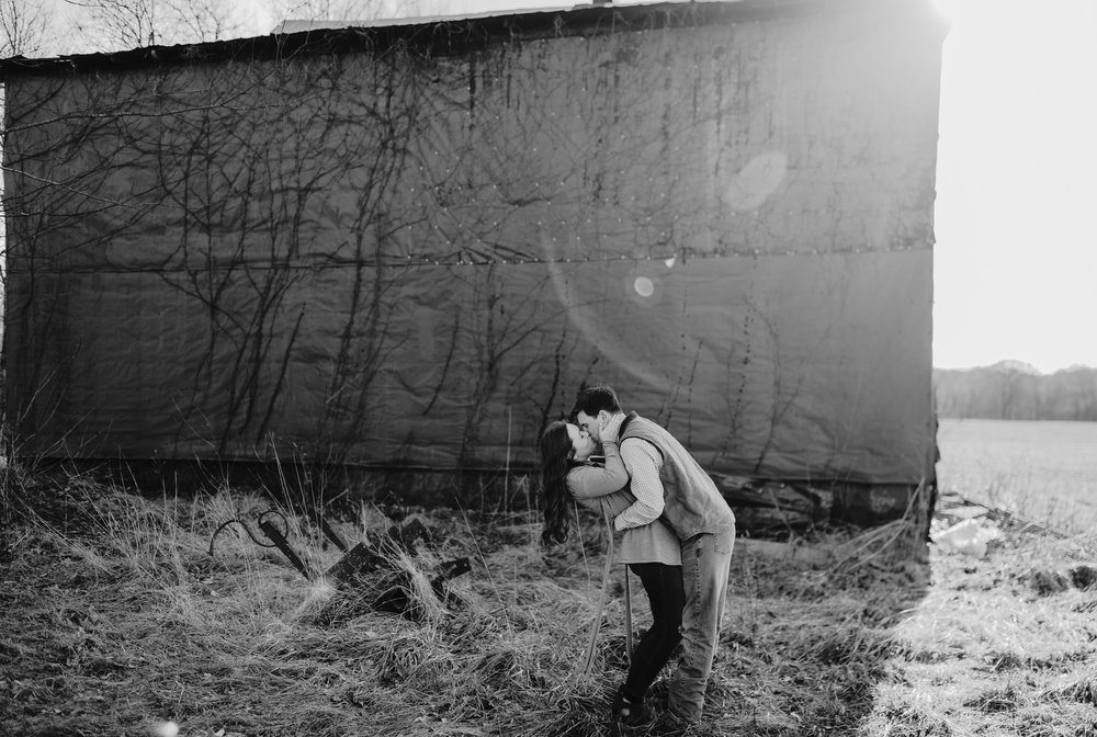 couple kissing in front of barn