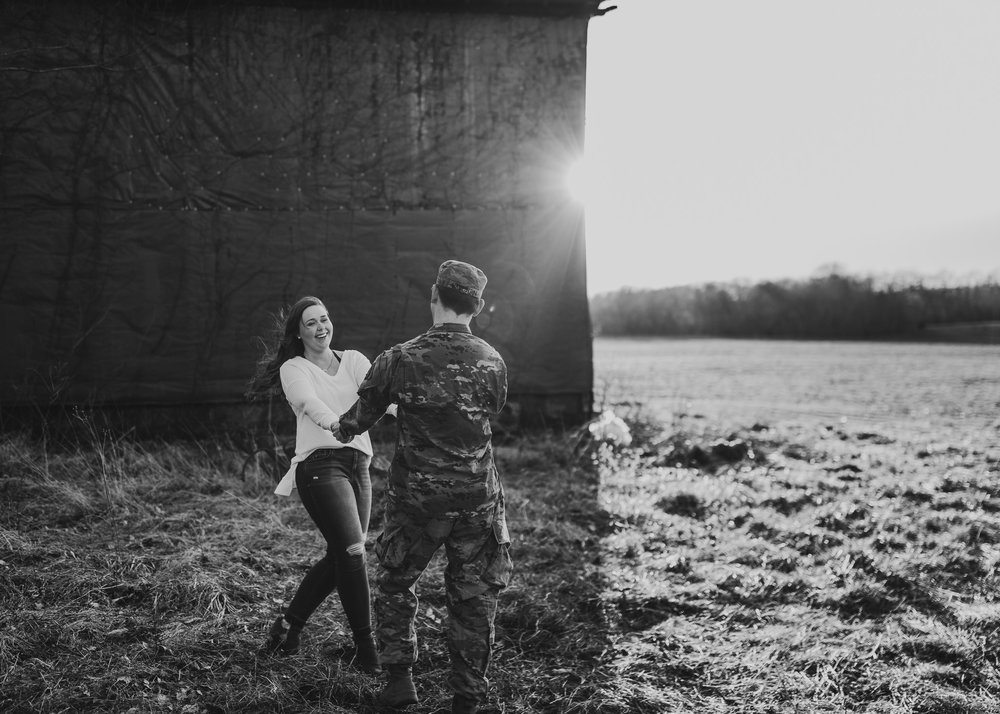 couple twirling in black and white and army uniform