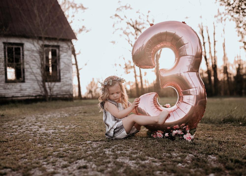 Birthday Girl Sitting with Balloon