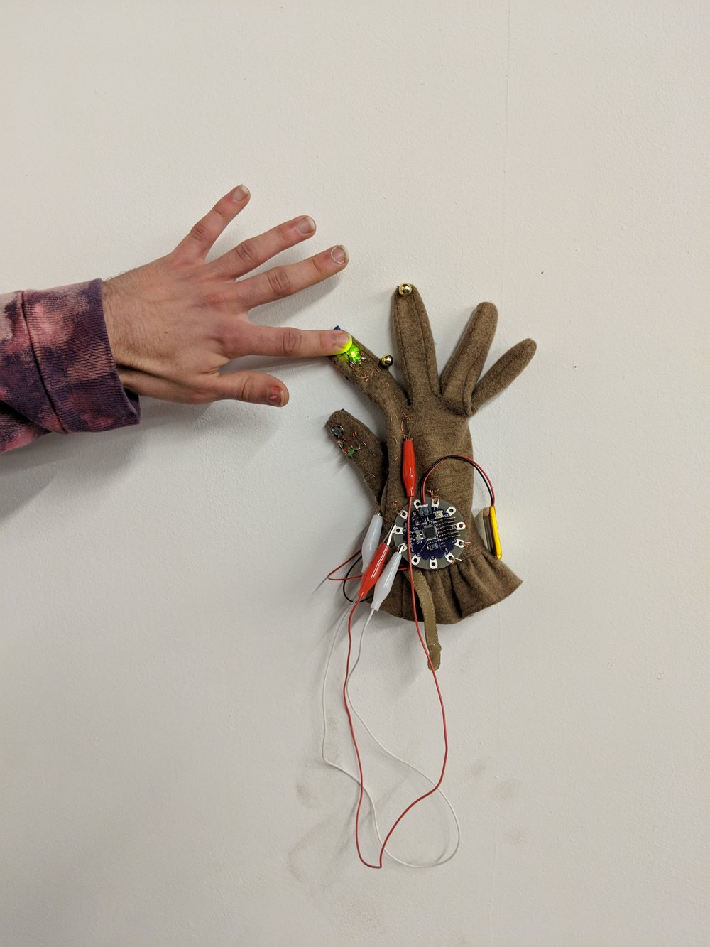 "Andrew Gangnes: ""Glove Prototype""  A glove used as an instrument to play sounds from Ableton and record them simultaneously. It has an embedded handmade pressure sensor on a finger tip that records information when you tap it on a surface (reverse engineering a beat pad)."
