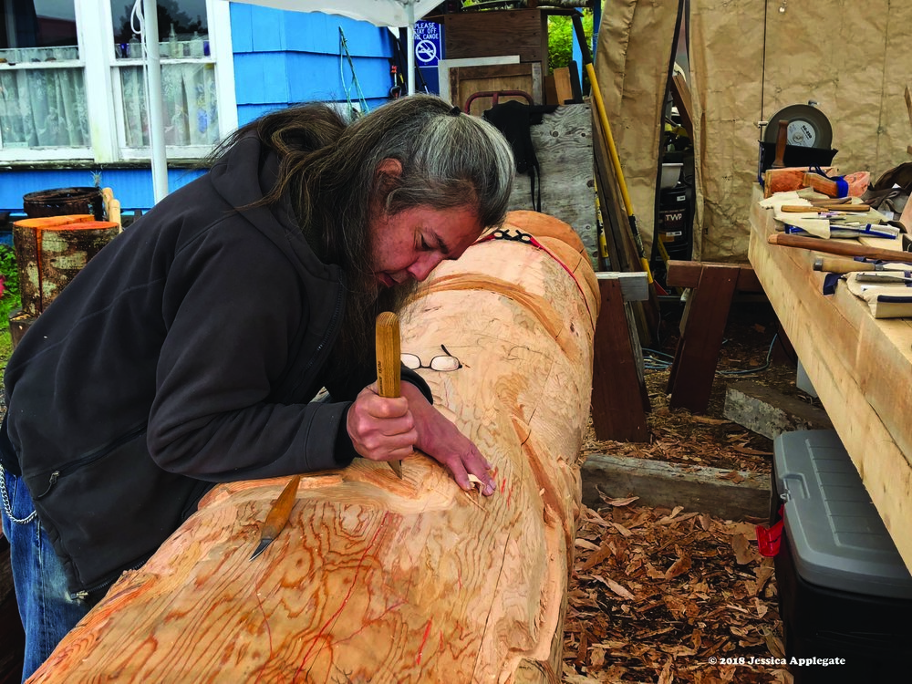 Tommy Joseph, a Tlingit artist in Sitka, carves a totem pole out of an Alaska yellow cedar log.