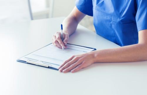close-up-of-doctor-or-nurse-writing-to-clipboard-PYA3KPB.jpg