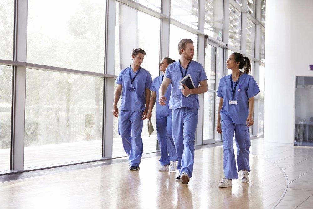 four-healthcare-workers-in-scrubs-walking-in-PWJFVZK.jpg