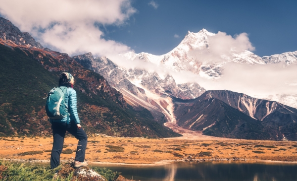 standing-young-woman-with-backpack-and-mountains-PL9PP2Y.jpg
