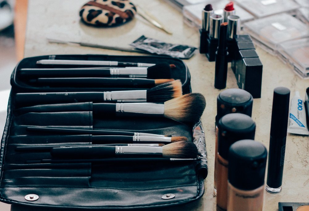 An assortment of makeup brushes and makeup on a counter