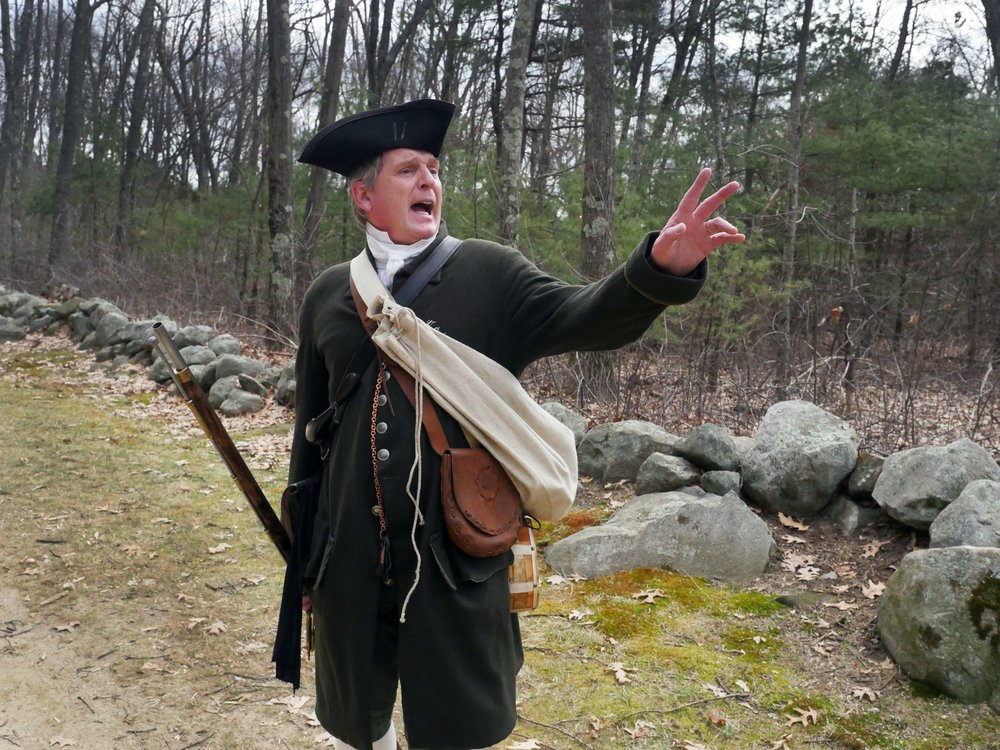 "Lincoln, MA - April 14th, 2018 - Hannes Klein heckles a passer byer wearing a red jacket, the color of the ""regulars,"" also known as the British in the Revolutionary War. Klein sees his job as a reenactor as much more than just reenacting the events saying, ""we as reenactors our job is actually to reenact history and also be a translator for history."""